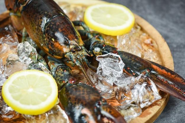 Verse kreeft schelpdieren in het visrestaurant voor gekookt voedsel rauwe kreeft op ijs en citroen op een zwarte stenen tafel