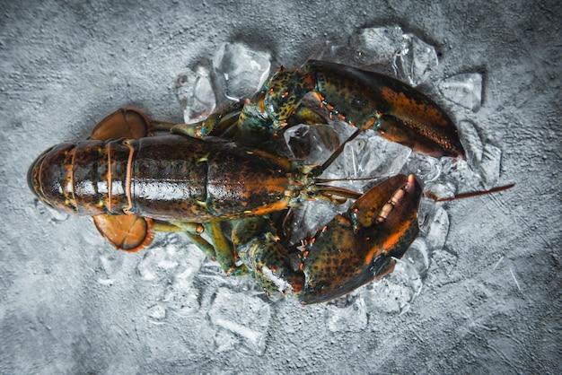 Verse kreeft schelpdieren in het visrestaurant voor gekookt voedsel rauwe kreeft op ijs op een zwarte stenen tafel