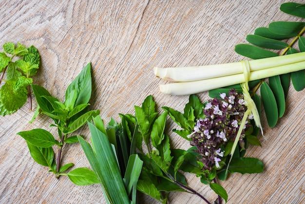 Verse kruiden en specerijen met zoete basilicum citroengras heilige basilicum pepermunt blad op houten