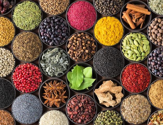 Verse kruiden en specerijen voor voedsel. kleurrijke specerijen als muur, bovenaanzicht. veel kruiden in kopjes, op tafel