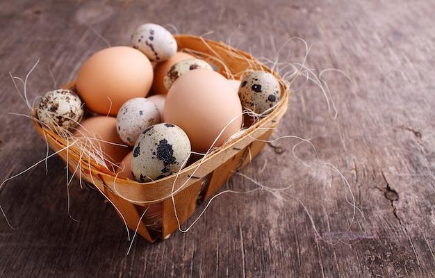 Verse landbouwereieren van kip en kwartels in een mand op rustieke achtergrond