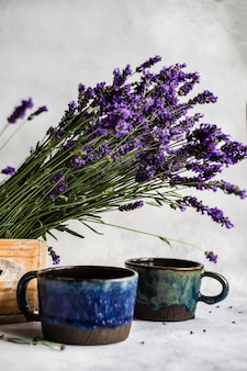Verse lavendelbloemen en kopjes thee met citroen op betonnen tafel