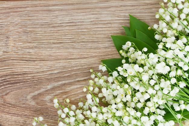 Verse lelie van de vallei flowersborder op houten achtergrond