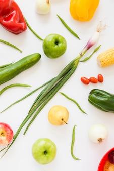Verse lente-ui; tomaten; komkommer; appel; peren; ui; groene paprika's en slabonen op witte achtergrond worden geïsoleerd die