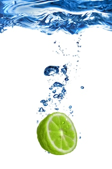 Verse limoen daalde in water met bubbels op wit wordt geïsoleerd