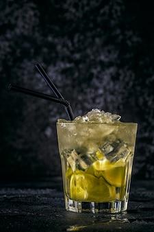 Verse limoencocktail met ijs op donkere achtergrond.