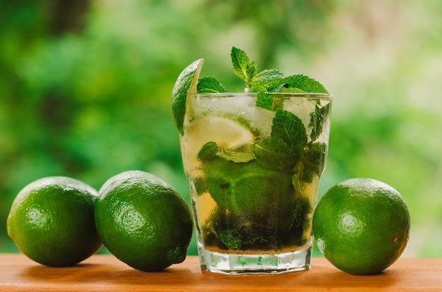 Verse limoenen en limonade op houten tafel