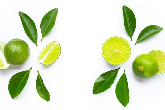Verse limoenen (lemmetjes) met groene bladeren op een witte achtergrond. kopieer ruimte voor tekst of product