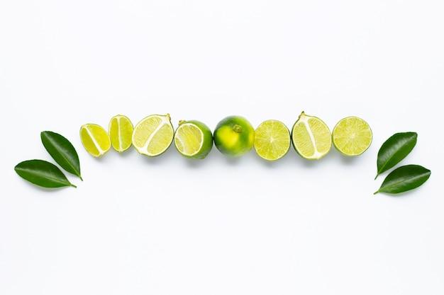 Verse limoenen met bladeren die op wit worden geïsoleerd