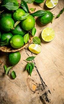 Verse limoenen met bladeren in de mand. op houten tafel.