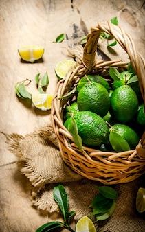 Verse limoenen met bladeren in de oude mand.