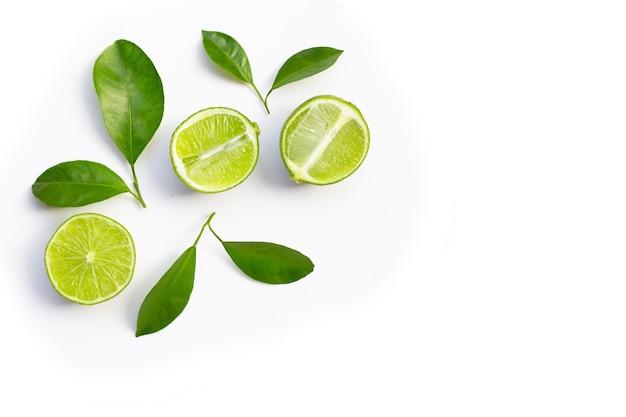 Verse limoenen met groene bladeren op een witte achtergrond. bovenaanzicht