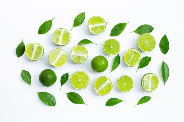 Verse limoenen met groene bladeren op witte achtergrond. bovenaanzicht