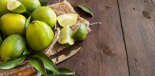 Verse limoenen met mes op een houten tafel