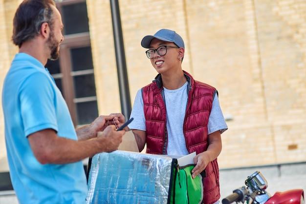 Verse lunch jonge vrolijke aziatische koerier met thermotas die voedsel levert aan klant op scooter