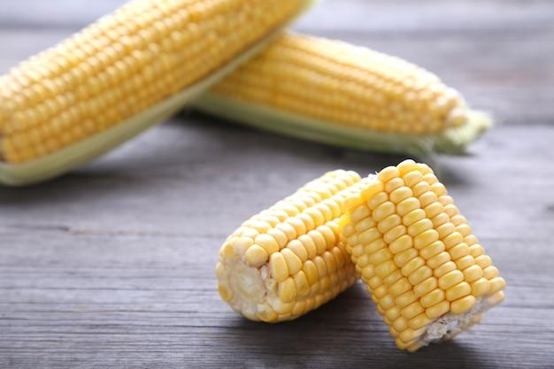Verse maïs op een grijze houten achtergrond. stukjes maïs op een grijze achtergrond