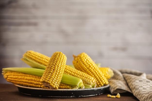 Verse maïs op kolven op donkere houten tafel. met kopie ruimte