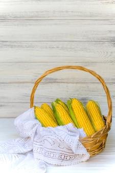 Verse maïskolven in rieten mand. onbehandelde maïskolven. verse maïsgroente in mand. geoogst graan in rieten mand, vers geplukte maïsoren uit in landbouw selectief gebiedslandschap
