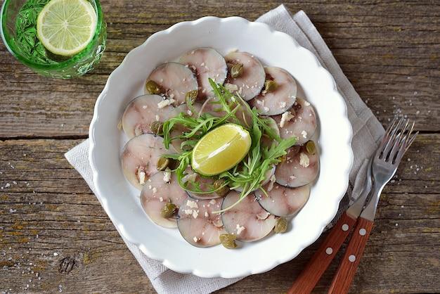 Verse makreel carpaccio met kappertjes, parmezaan, rucola en olijfolie