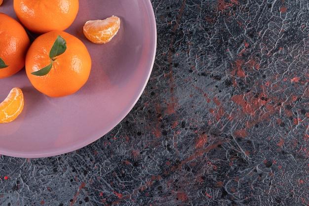 Verse mandarijn op een bord, op de gemengde tafel.