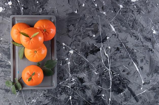 Verse mandarijn op een houten plaat, op de gemengde tafel.