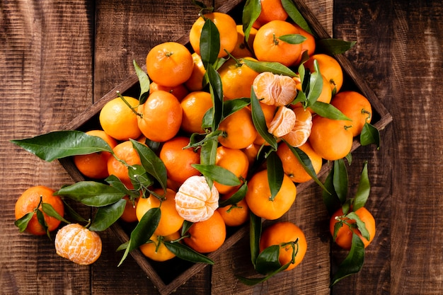 Verse mandarijn sinaasappelen fruit of mandarijnen met bladeren in houten kist, bovenaanzicht