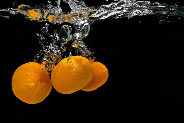 Verse mandarijnen die in water met bellen op zwart vallen