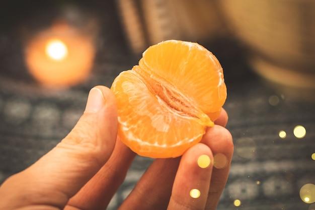 Verse mandarijnen eten op een gezellige winterachtergrond, man met mandarijn hoge kwaliteit foto