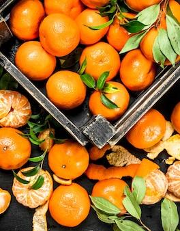 Verse mandarijnen in een doos op zwart bord.