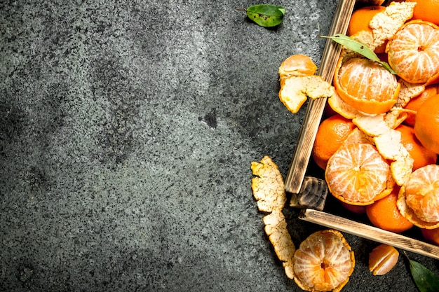Verse mandarijnen in een oude doos op rustieke tafel.