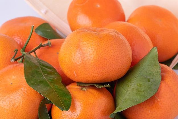 Verse mandarijnen, mandarijnen, met bladeren, in een houten bakje-mand omgedraaid met wit oppervlak.