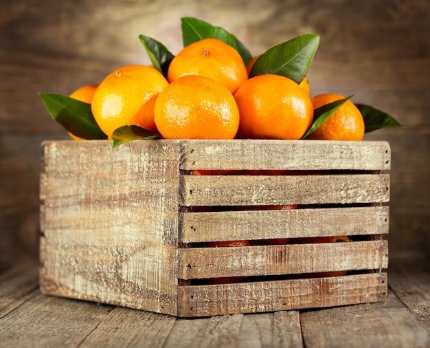Verse mandarijnen met bladeren in houten kist
