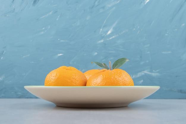 Verse mandarijnen met bladeren op groene plaat