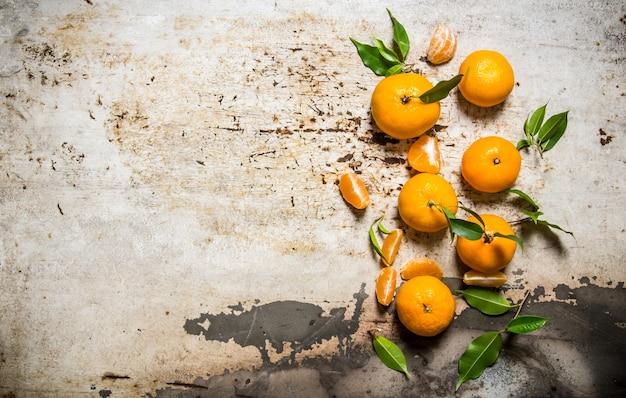 Verse mandarijnen met bladeren op rustieke tafel. bovenaanzicht