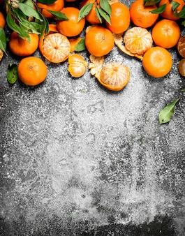 Verse mandarijnen met bladeren op rustieke tafel.