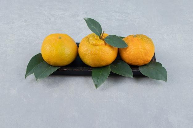 Verse mandarijnen met bladeren op zwarte plaat.