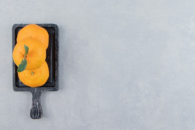 Verse mandarijnen met bladeren op zwarte snijplank.