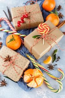 Verse mandarijnen met bladeren, zuurstokken, geschenkverpakkingen in kraftpapier en kruiden - kaneel, anijs en kruidnagel