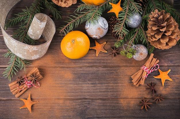 Verse mandarijnen met kruiden en kerstdecor met kerstboom op donkere oude houten tafel. rustieke stijl. winter vakantie concept. bovenaanzicht met ruimte voor tekst