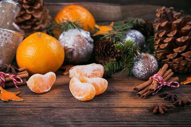 Verse mandarijnen met kruiden en kerstdecor met kerstboom op donkere oude houten tafel. rustieke stijl. winter vakantie concept.