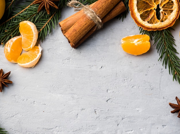 Verse mandarijnen met takken van kerstboom, steranijs kaneel op grijs beton, kopie ruimte