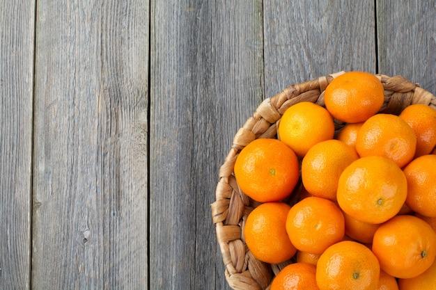 Verse mandarijnen op een bord gemaakt van rotan. bovenaanzicht. rustieke stijl. selectieve aandacht.