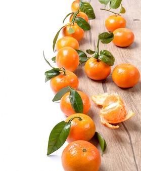 Verse mandarijnen op hout dat op wit wordt geïsoleerd