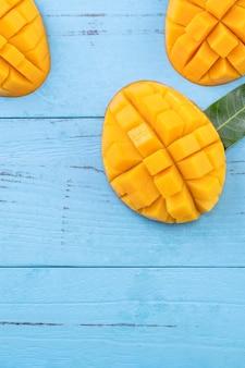 Verse mango, mooi gehakt fruit met groene bladeren op donkere houten tafel achtergrond. tropisch fruit ontwerpconcept. plat leggen. bovenaanzicht. ruimte kopiëren