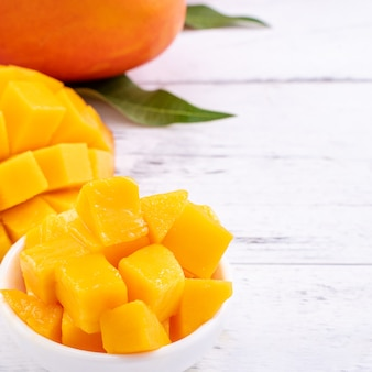Verse mango, mooi gehakt fruit met groene bladeren op lichte houten tafel achtergrond. tropisch fruit ontwerpconcept, close-up, kopieer ruimte.