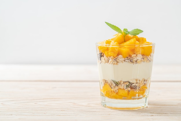 Verse mangoyoghurt met granola in glas - gezonde voedselstijl