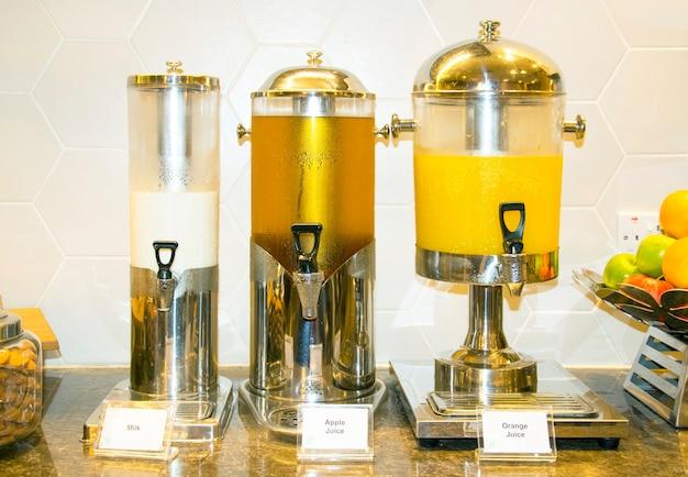 Verse melk, appelsap, sinaasappelsap in waterkoeler voor het raden van een seminar in het hotel.