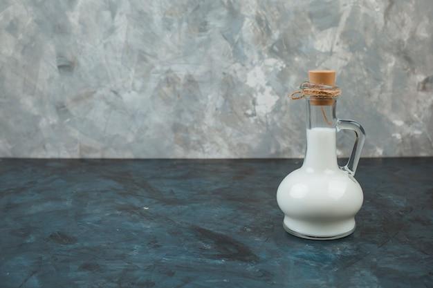 Verse melk in een kruik op de donkerblauwe achtergrond