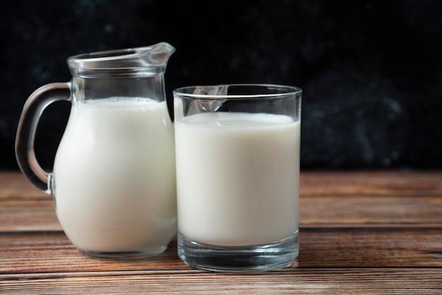 Verse melk in een mok en kruik op houten tafel.
