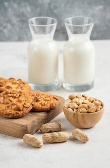 Verse melk, pinda's en lekkere koekjes op marmeren tafel.